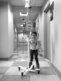 "Natalie was pushing her IV pole as she wanted to ""take a walk"" around the clinic. She looks so big in this photo. It was a ""sleepy room"" day which meant a spinal of methotrexate and an aspirate to make sure her fluid is still clear of leukemia."